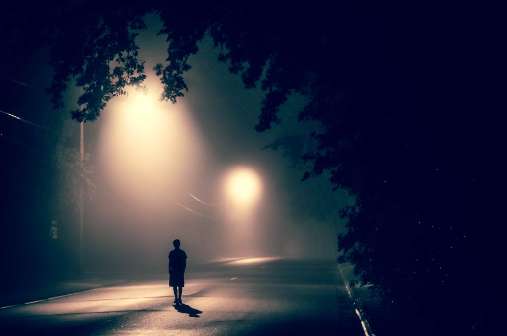 person walking under lamplight at night