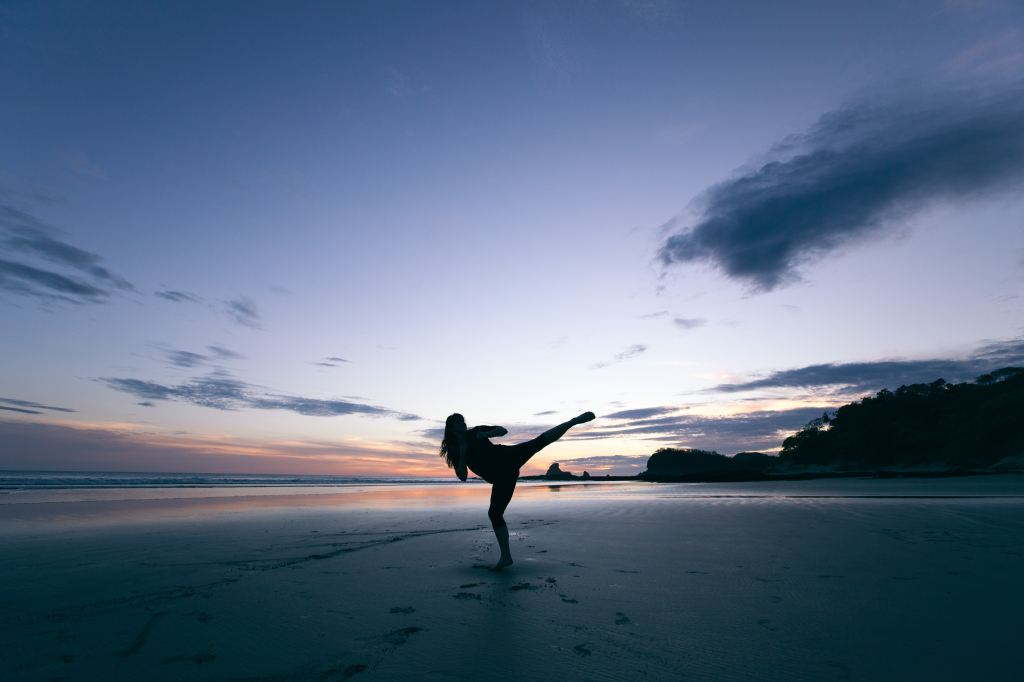 Woman kickboxing on the beach