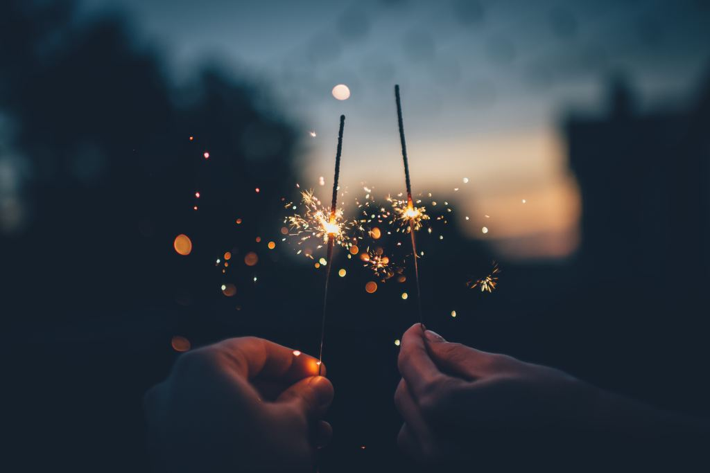 two people holding sparklers next to one another