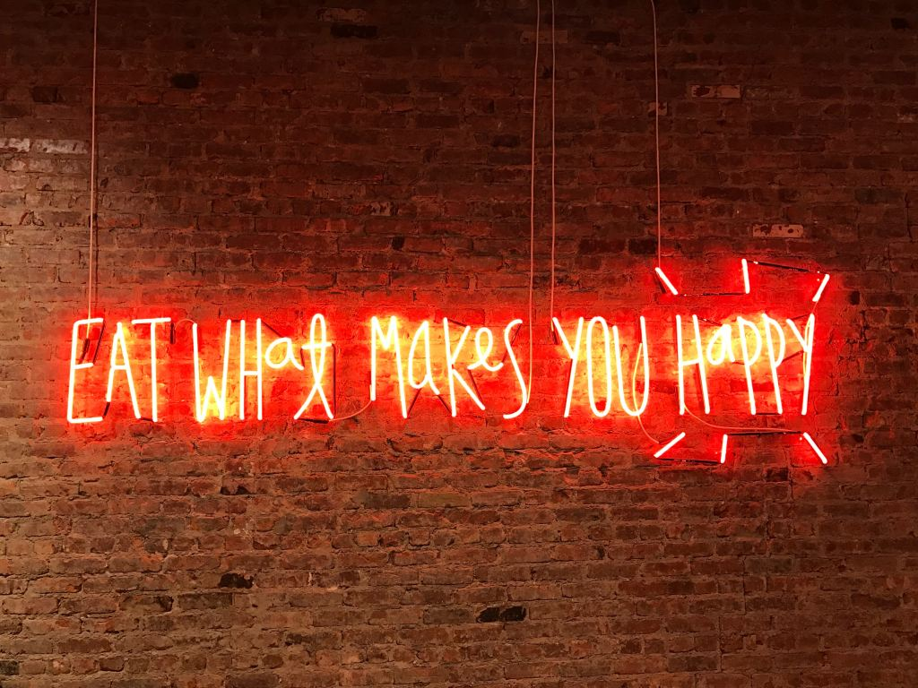 neon sign that says eat what makes you happy