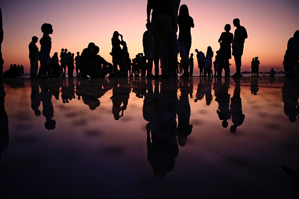 group of people at sunset with reflections in sand