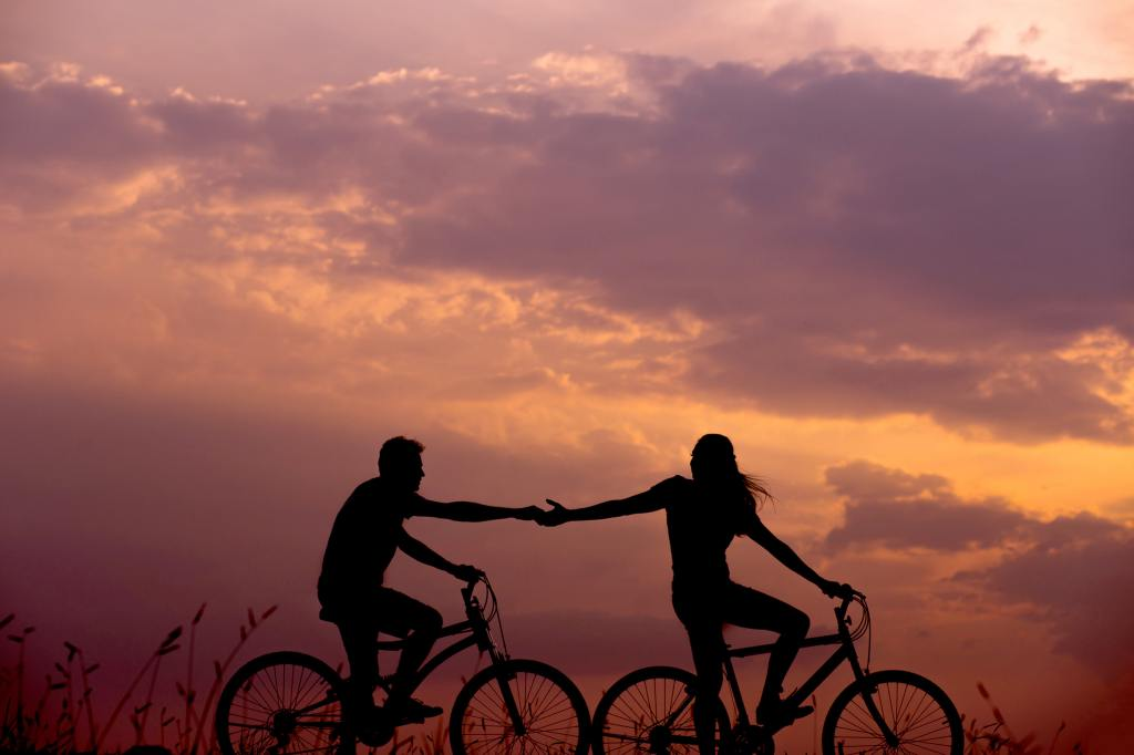 two people holding hands on bikes