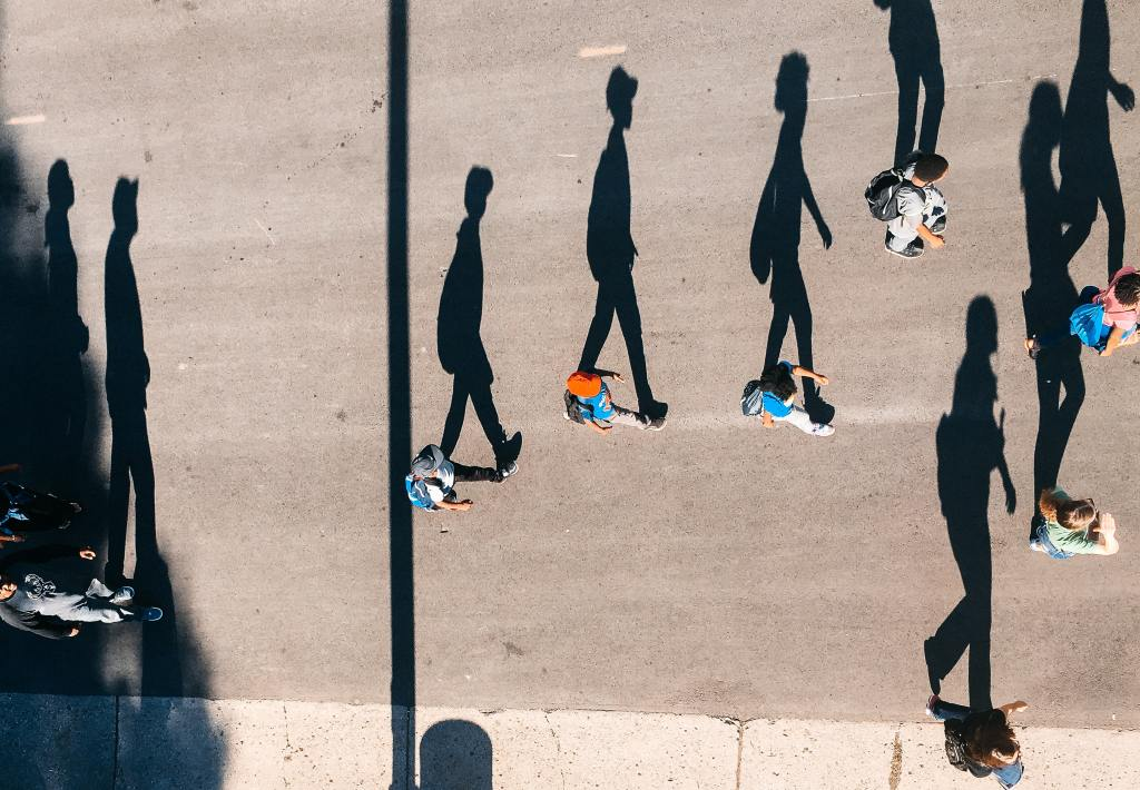 people with long shadows walking on a road