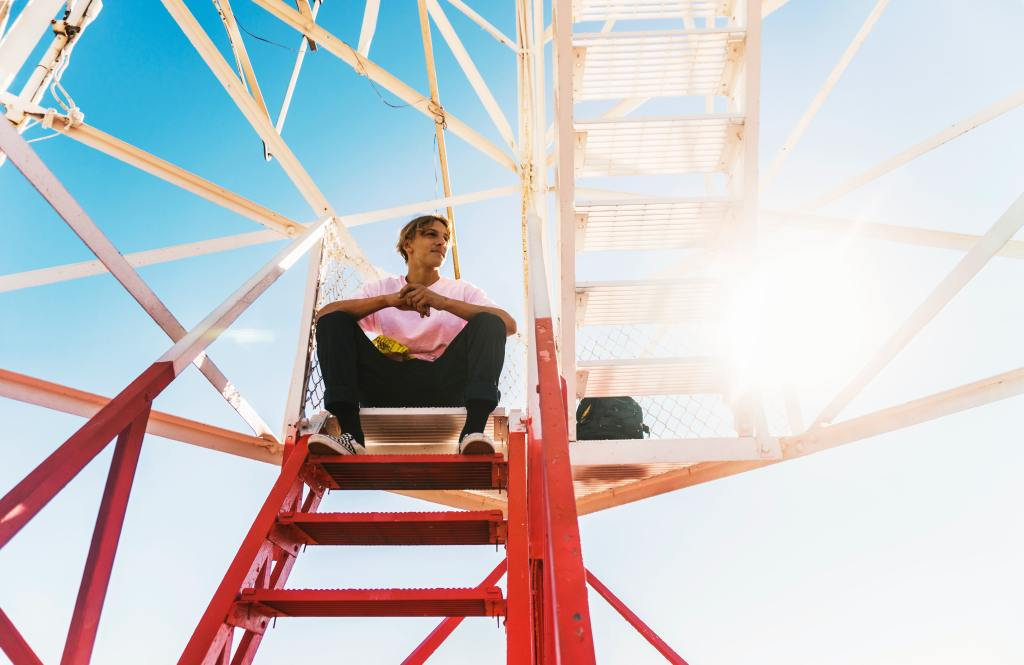 man sitting on a red and white metal staircase
