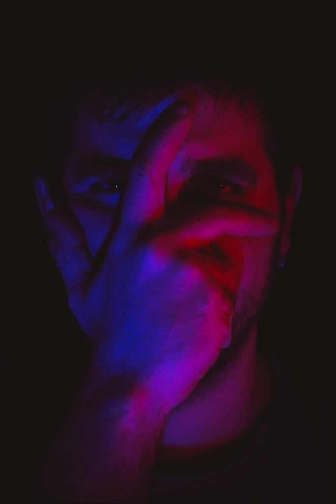 man with hand over face in the dark