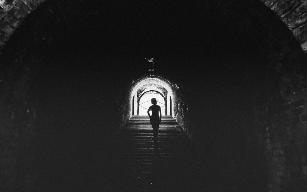 woman standing in a dark tunnel with light at the other end