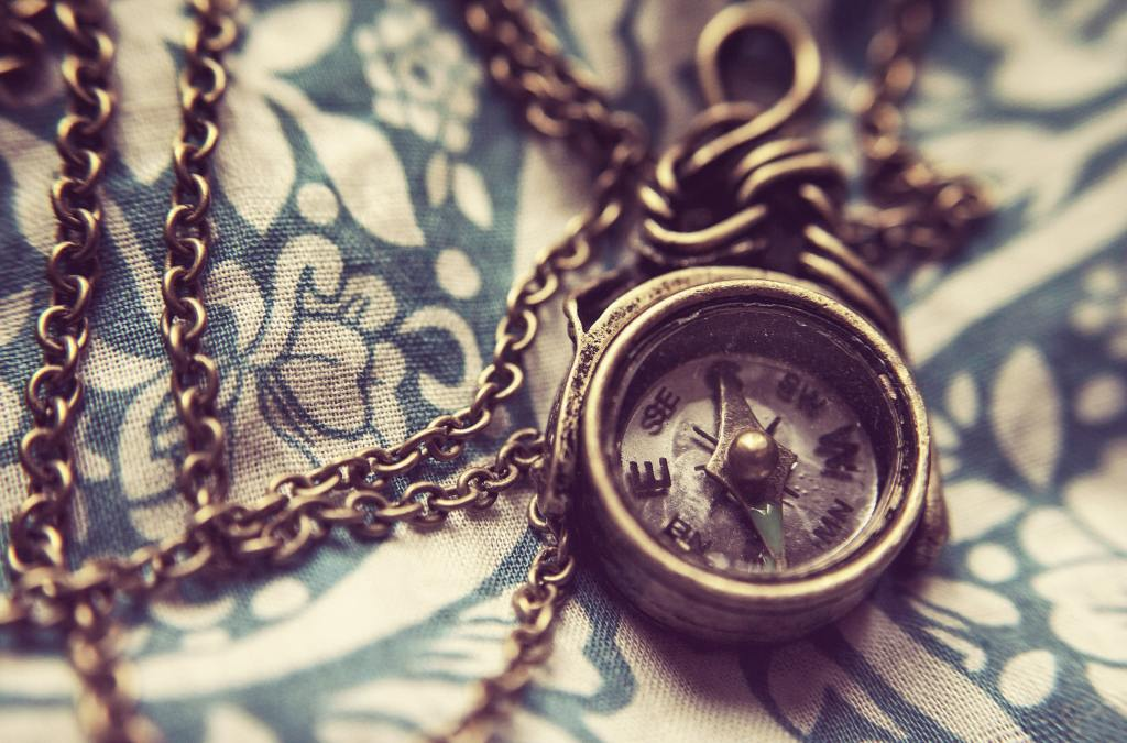 bronze compass necklace on a blue and white fabric backdrop