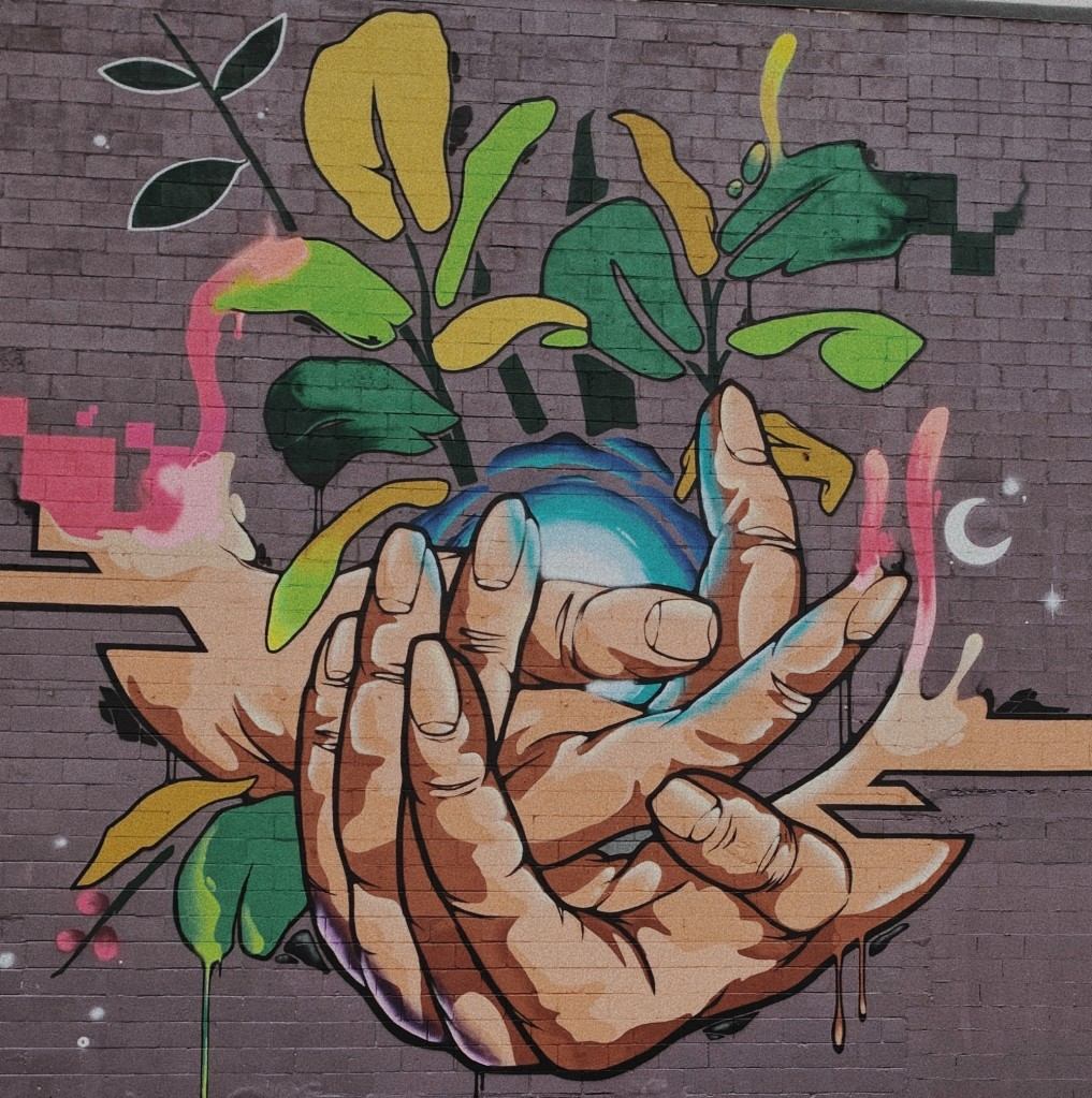 colorful mural of hands embracing a blue orb