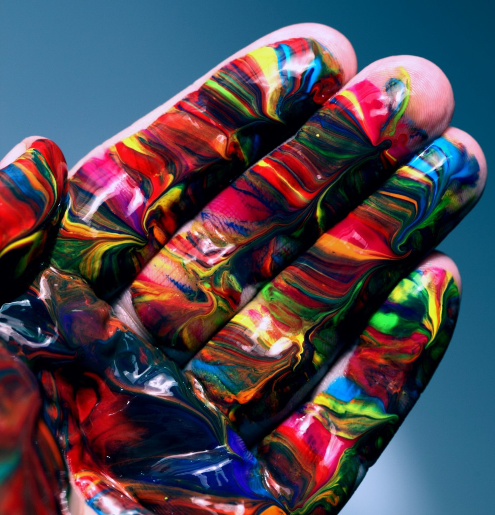 hand covered in rainbow swirls of paint