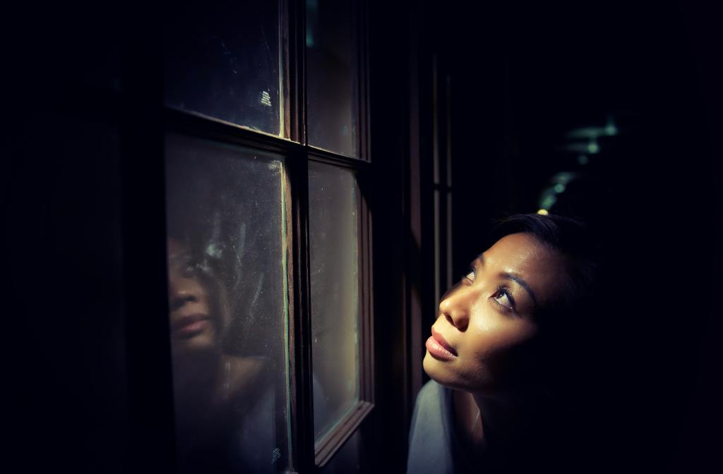 woman peering up through a window