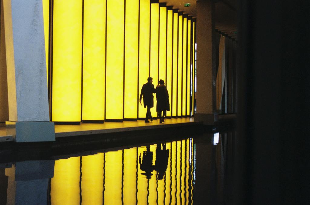 Two people walking along a lit yellow wall reflecting in a pool of water