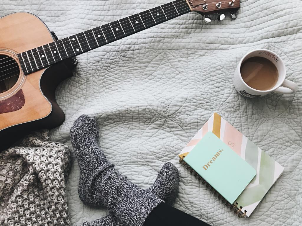 person sitting with guitar, coffee, and journals