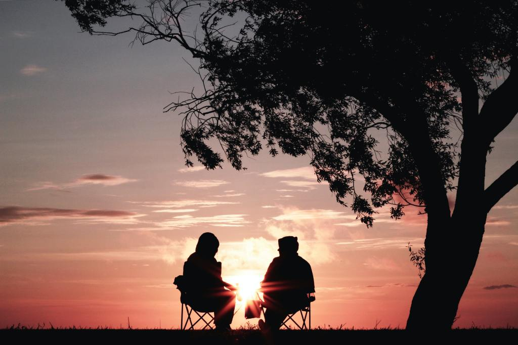 two people sitting outside under a tree in the sunset