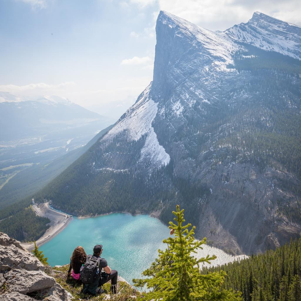 Two people sitting down viewing a mountain and lake in the distance
