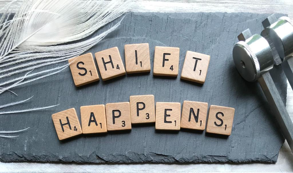 "Scrabble letters on a slate that read ""SHIFT HAPPENS"""