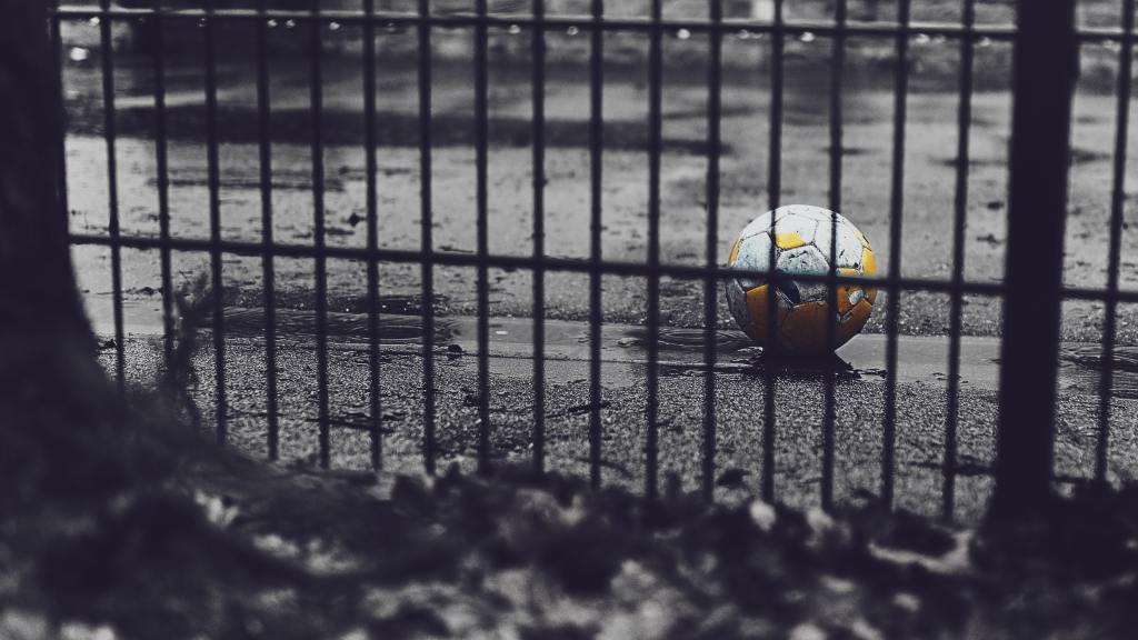 soccer ball outside of a black iron gate