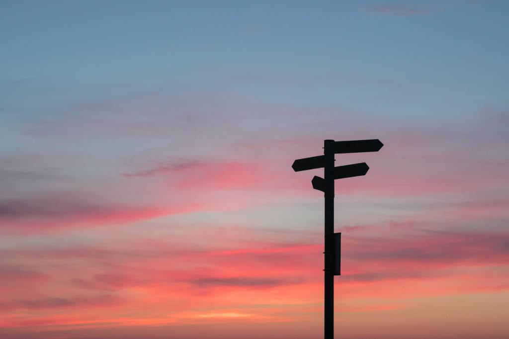 signpost pointing in various directions against a pink and blue sunset