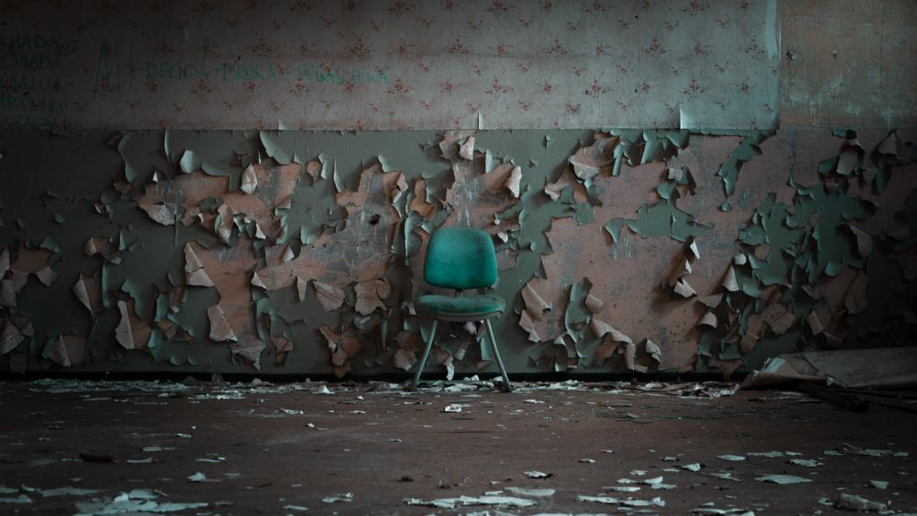turquoise chair against a wall with peeling wallpaper