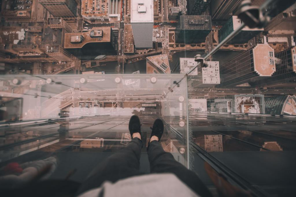 person standing on balcony with see-through glass floor