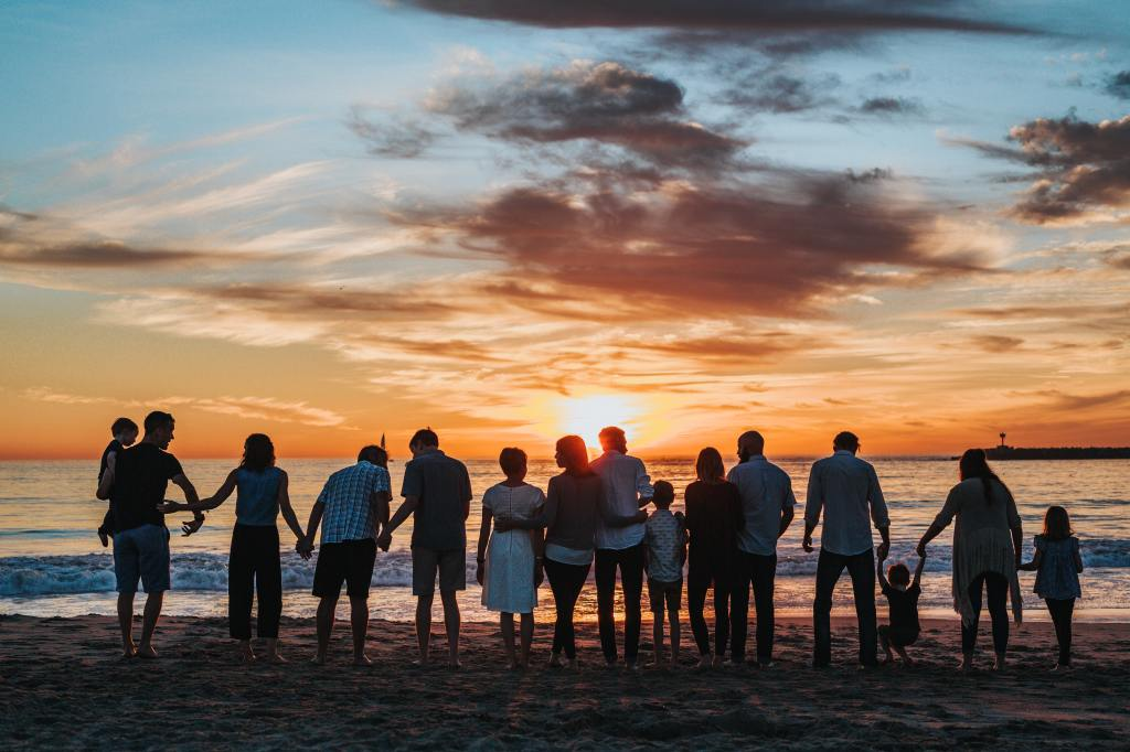 reunion of people holding hands on a beach at sunset
