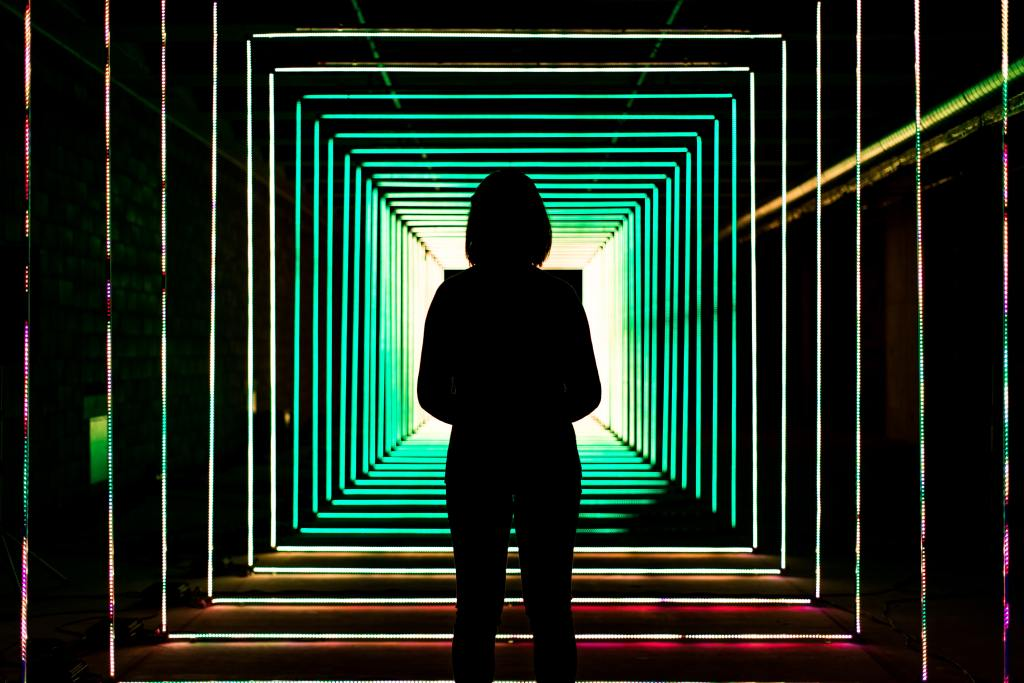 Silhouette of a woman's back who is standing in front of illuminated rainbow squares