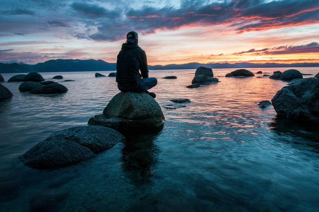 Photo of a person taken from behind who is sitting on a rock in the ocean and looking forward into the sunset