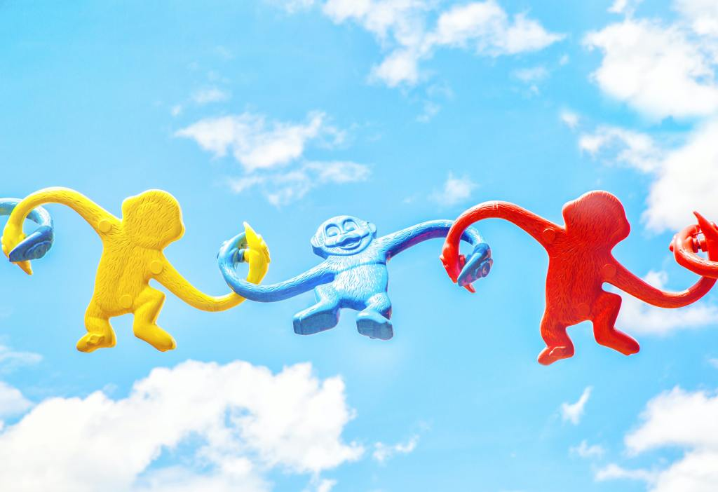 Three plastic toy monkeys linked together by the arms